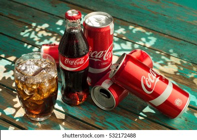 MINSK, BELARUS-AUGUST 26, 2016: Glass of Coca-Cola with ice, can and bottle of Coca-Cola on wooden background. Coca-Cola is a carbonated soft drink sold in stores, throughout the world.