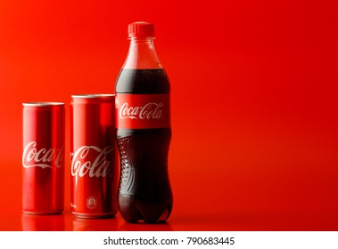 MINSK, BELARUS-JANUAR 10, 2018: Can and bottle of Coca-Cola on red background. Coca-Cola is a carbonated soft drink sold in stores, restaurants, and vending machines throughout the world.