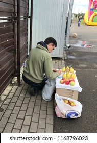 MINSK, MINSKAYA, BELARUS 29, AUGUST 2018; Unauthorized sale of fruit on the street. The man laid out his goods: apples and pears. He writes a price on the plate.