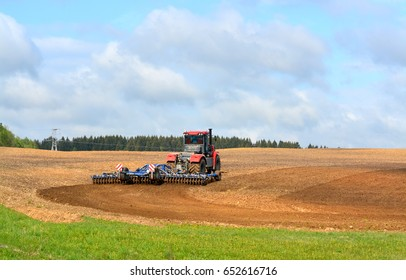 MINSK REGION, BELARUS - May 16, 2017: The tractor harrows the ground in the village. Spring field works.
