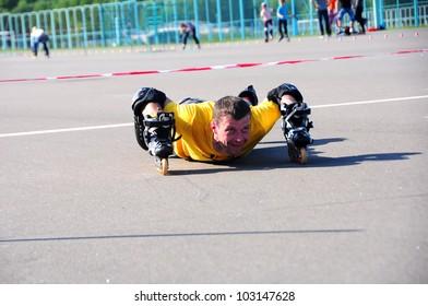 MINSK,BELARUS -MAY 19: School Roller Cup 2012 - Stage 1 (FSK). Sasha Popelsky, instructor FSK, put roller Skates on hands on May 19, 2012 in Minsk, Belarus