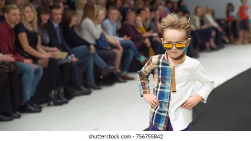 MINSK/BELARUS – OCTOBER  25 2017: Kids Fashion Day - one beautiful boy posing on catwalk  at Belarus Fashion Week  Spring – Summer 2018.  In the background sit the audience
