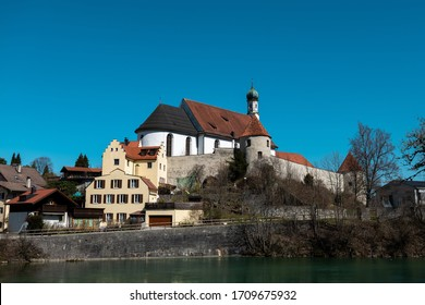 Minster of the franciscans in the city of fuessen wit parts of the old city wall and the river Lech in the foreground during spring