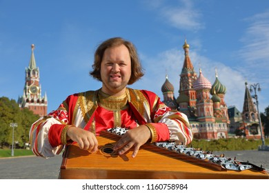 The minstrel in traditional Russian clothes plays an old Russian musical instrument gusli on the background of the Kremlin and St. Basil's Cathedral on red Square. Moscow, Russia