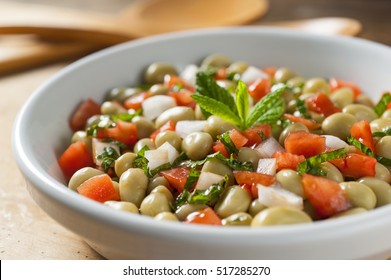 mint broad bean salad with tomatoes and onions in a white bowl and wooden cuttlery at the background front shot