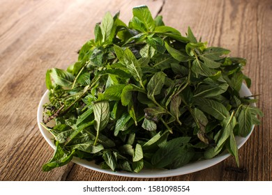 Mint. Bunch of Fresh green organic mint leaf on wooden table closeup. Selective focus. On natural wooden background