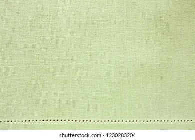 Mint candy colour, pastel green woven fabric with decorativer border, laid out flat and shot from above as a background design element