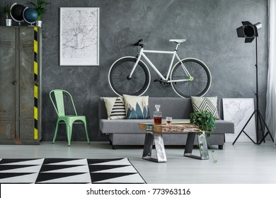 Mint chair next to white bicycle above grey sofa in guy living room with industrial designer table