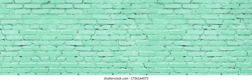 Mint color painted brick wall wide texture. Old pastel green rough brickwork background
