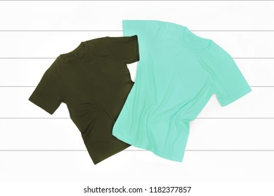 Mint and Dark Green T-shirts on a White Wooden Background - Flat Lay