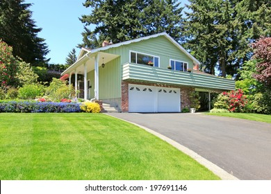 Mint house with columns entrance porch, brick wall trim and garage. View of driveway and green lawn with blooming flower bed