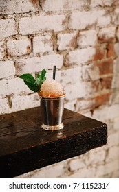 A mint julep cocktail on a wooden surface against white brick background
