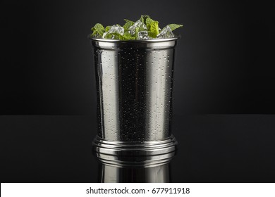Mint Julep.In a silver julep gentle muddle the mint, sugar and water. Fill the glass with cracked ice, add Bourbon and stir well until the glass is frost. Garnish with a mint spring.