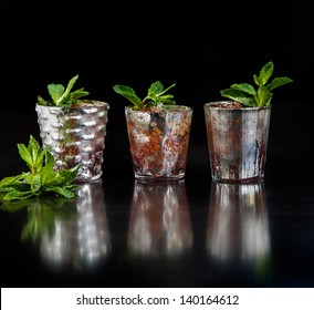 Mint Juleps in Decorative Silver Glasses on a dark reflective wood background with fresh sprigs of mint