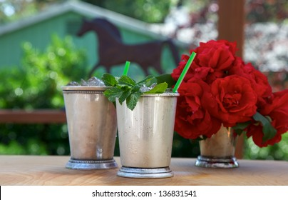 Mint juleps in traditional silver cups with red roses and horse shape in background
