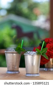 Mint juleps in traditional silver mint julep cups, red roses and horse silhouette in background, vertical