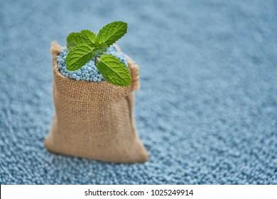 Mint leaves in gunny sack on blur (NPK) fertilizer  background.