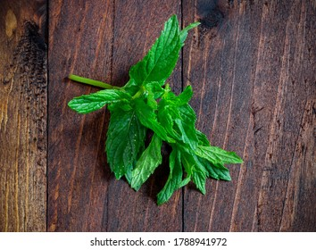 mint leaves on old wooden table with water drops