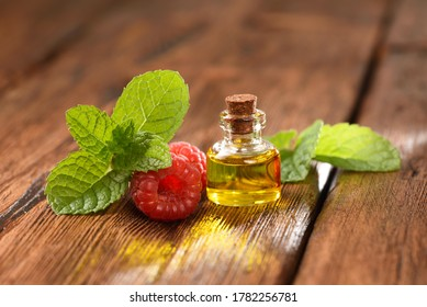 Mint leaves and raspberry berry on a wooden table, raspberry oil.