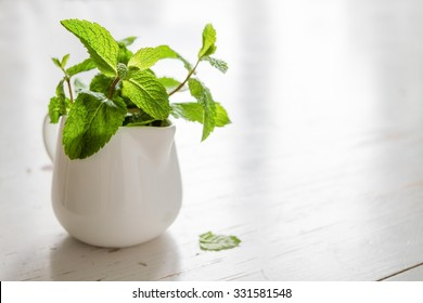 Mint leaves in white jar, white wood background