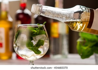 Mint leaves in wineglass. Bottle with yellow liquid. Elderflower syrup for hugo cocktail. Preparation of beverage at bar.