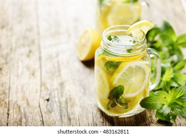 Mint lemonade in mason jars on rustic wooden table with copyspace
