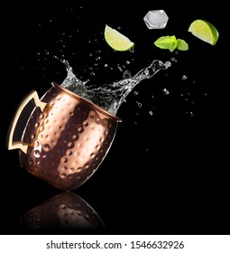 mint, lime and ice cube falling into a splashing moscow mule isolated on black