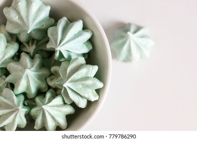 Mint meringue cookies on a white background in a white deep plate. The photo can be used in the meringue recipe.
