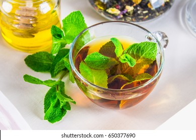 Mint tea in a cup, a jar of honey, a cookie in a jar, on a white tray in bed