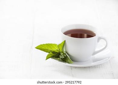 Mint tea on white on wooden background