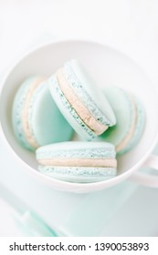Mint or tiffany color macaron or macaroon dessert with vanilla cream in white cup. Pastel toned. Copy space