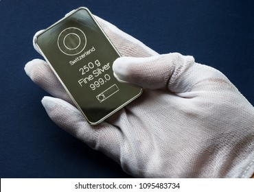 Minted silver bar in the hand, dressed in a white protective glove. On a blue background.