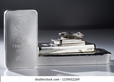 Minted silver bars and coins against a gray background. Selective focus.
