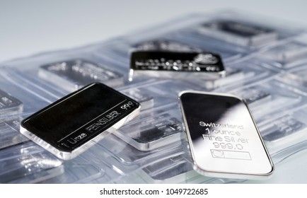 Minted silver bars weighing one troy ounce in plastic packaging and unpacked. Selective focus. feinzilber is fine silver