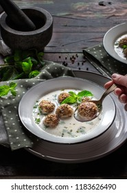 Minty turkish yogurt soup with meatballs on wooden table. Selective focus.