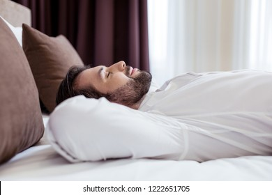 Minute to relax. Joyful pleasant man lying on the bed while enjoying his relaxation