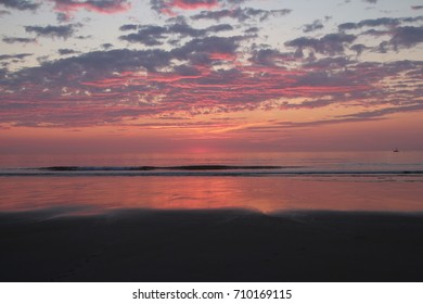Minutes Before Sunrise on an East Coast Beach - Pink and Purple Clouds - Partly Cloudy Sky - Waves Crashing