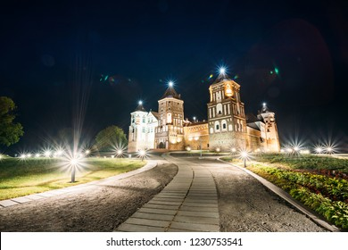 Mir, Belarus. Mir Castle Complex In Evening Illumination Lighting. Famous Landmark, Ancient Gothic Monument Of Feudalism Under Blue Night Sky. UNESCO Heritage. Panorama, Panoramic View Shot