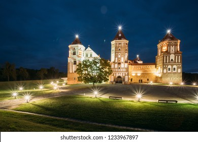 Mir, Belarus. Mir Castle Complex In Evening Illumination Lighting. Famous Landmark, Ancient Gothic Monument Of Feudalism Under Blue Night Sky. UNESCO Heritage.