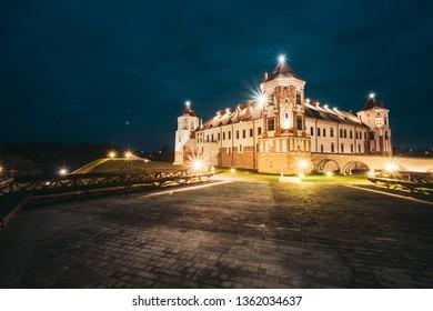 Mir, Belarus. Castle Complex Mir In Evening Or Night Illumination. Cultural Monument, UNESCO World Heritage Site. Famous Landmark And Popular Destination In Night Llight Lighting.