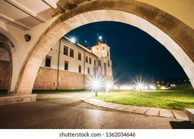 Mir, Belarus. Castle Complex Mir In Evening Night Illumination. Cultural Monument, UNESCO World Heritage Site. Famous Landmark And Popular Destination In Night Llight Lighting. View From Under Bridge.