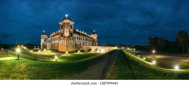 Mir, Belarus. Castle Complex Mir In Evening Night Illumination. Cultural Monument, UNESCO World Heritage Site. Famous Landmark And Popular Destination In Night Llight Lighting. Panorama Panoramic View