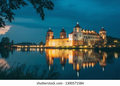 Mir, Belarus. Night Scenic View Of Mir Castle In Evening Illumination With Glow Reflections On Lake Water. UNESCO Heritage Site. Famous Landmark, Ancient Gothic Monument Of Feudalism