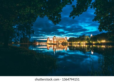 Mir, Belarus. Night Scenic View Of Mir Castle In Evening Illumination With Glow Reflections On Lake Water. UNESCO World Heritage Site. Famous Landmark, Ancient Gothic Monument. Popular Destination.
