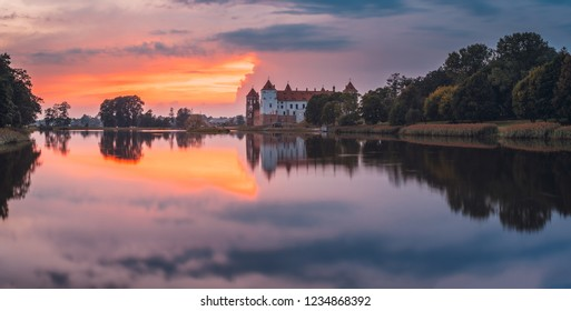 Mir, Belarus. Picturesque View Of Castle Complex Mir During Sunset. Old Towers Are Reflected In Lake River Water. Cultural Monument, UNESCO Heritage. Famous Landmark