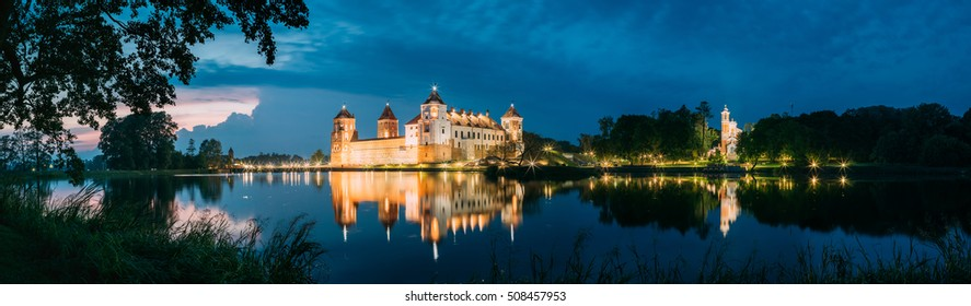 Mir, Belarus. Scenic Panoramic View Of Mir Castle Complex In Evening Illumination From Side Of Lake. Famous Landmark, Ancient Monument Under Blue Dramatic Sky.