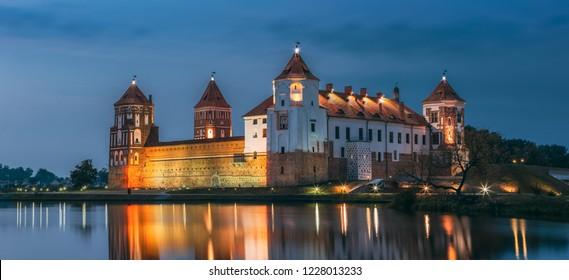Mir, Belarus. Scenic View Of Mir Castle Complex In Evening Illumination With Glow Reflections On Lake Water. UNESCO Heritage Site. Famous Landmark, Ancient Gothic Monument Of Feudalism. Panorama