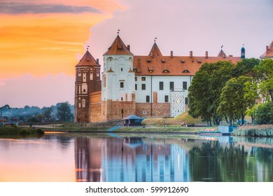Mir, Belarus. Scenic View Of Castle Complex Mir On Sunny Sunset Sky Background. Old Towers Are Reflected In Lake River Water