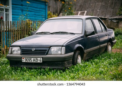 Mir, Belarus - September 1, 2016: Old rusty sedan car Opel Ascona C (1981-1988) parking in green grass on old wooden house background.