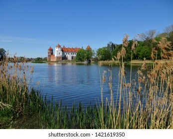 The Mir Castle Complex. Mir. Belarus. The landscape of the medieval castle on the backdrop of the lake and the blue Sunny sky